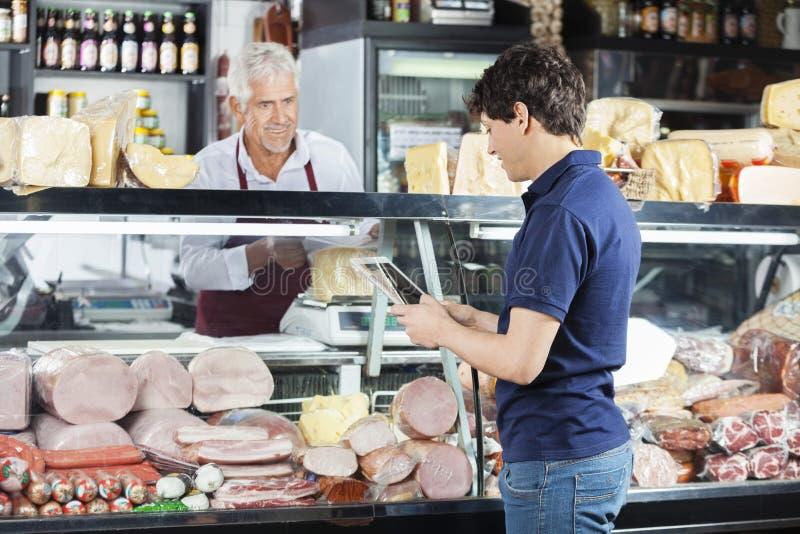 Mężczyzna Używa Cyfrowej pastylkę Podczas gdy sprzedawcy kocowania ser zdjęcie royalty free