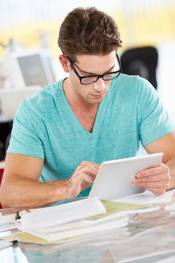 Mężczyzna Używa Cyfrowej pastylkę W Ruchliwie Kreatywnie biurze obraz stock