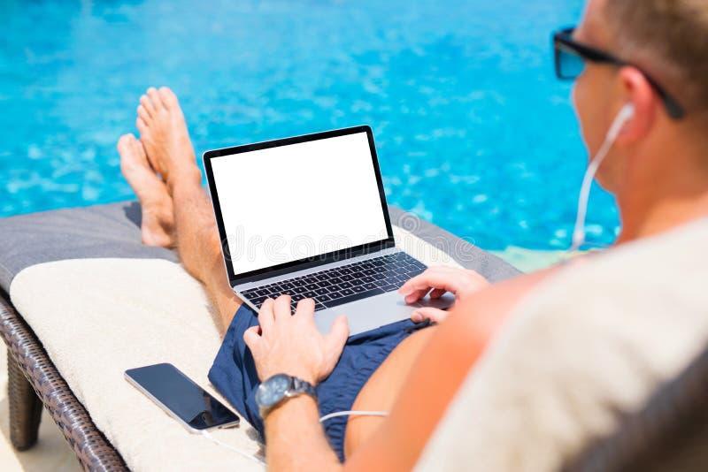 Mężczyzna używa laptop basenem Parawanowy mockup obrazy stock