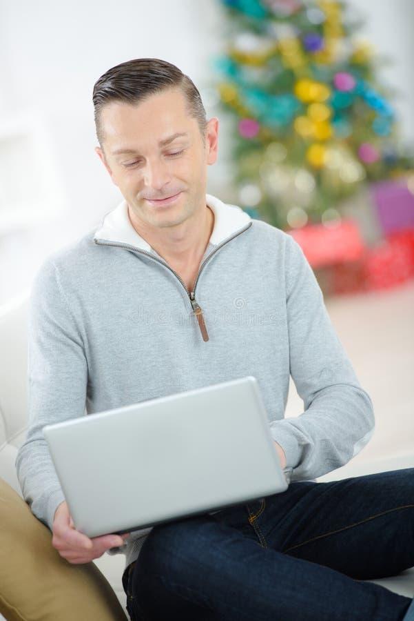 Mężczyzna używa laptop przy bożymi narodzeniami zdjęcie royalty free