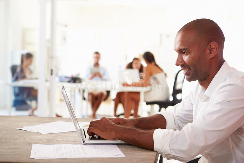 Mężczyzna Używa laptop W Nowożytnym biurze Zaczyna Up biznes fotografia royalty free