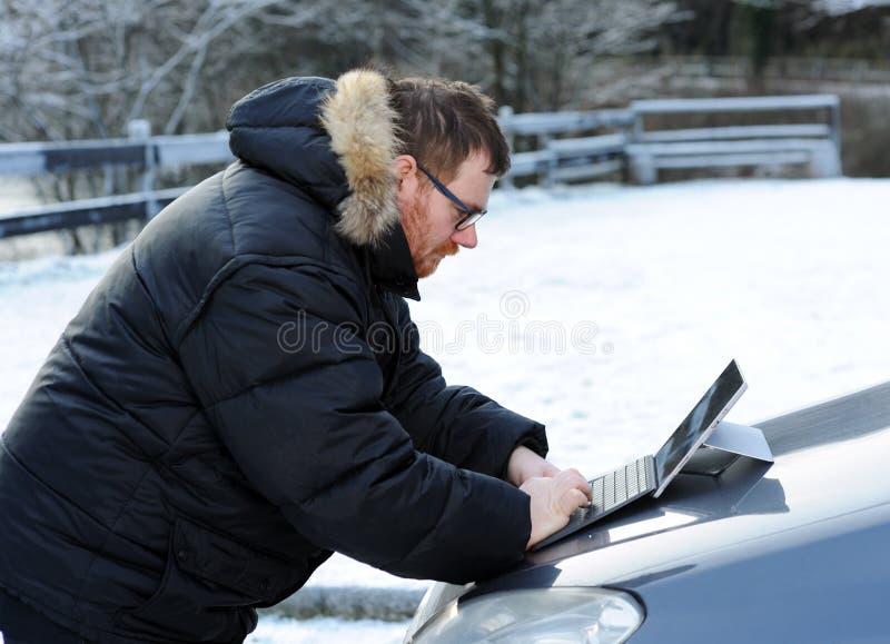 Mężczyzna używa pastylkę na samochodzie zdjęcie stock