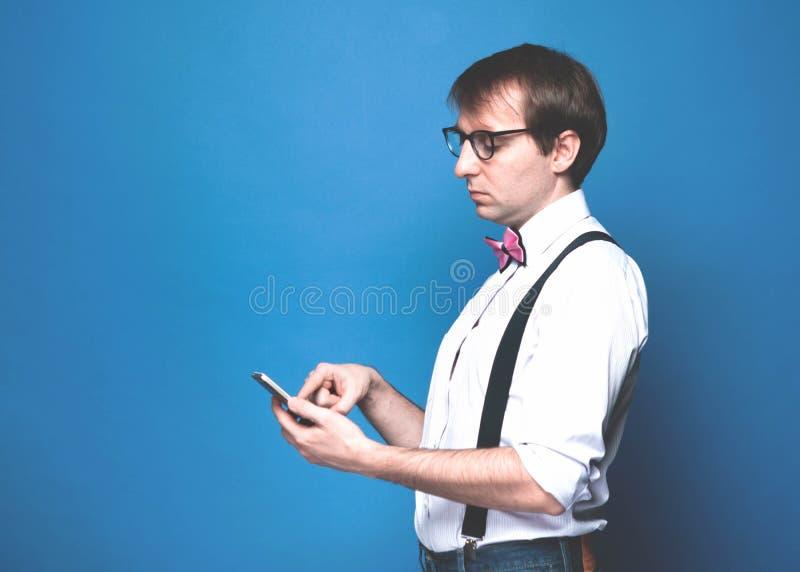 Mężczyzna używa smartphone na błękitnym tle zdjęcie royalty free