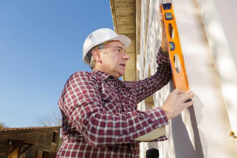 Mężczyzna używa spirytusowego poziom na zewnętrznej ścianie zdjęcia stock