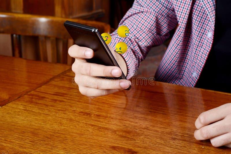Mężczyzna używa telefonu dosłania emojis zdjęcia royalty free