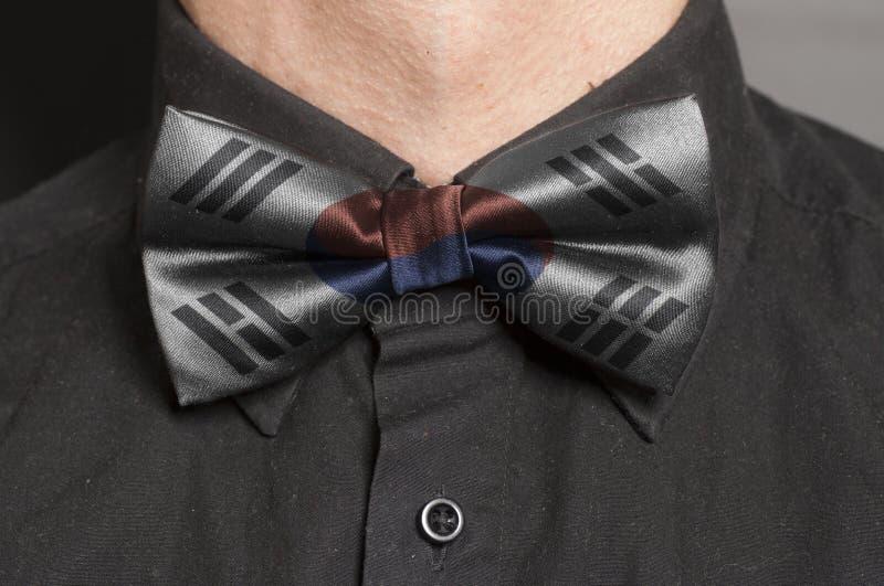 Mężczyzna Ubierająca Czarna koszula Z łęku krawatem z Poludniowo-koreańską flaga obraz stock