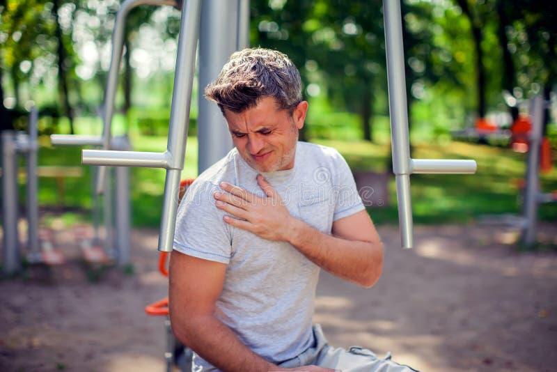 Mężczyzna uczucia ból w jego klatce piersiowej podczas sporta i trening w zdjęcie stock
