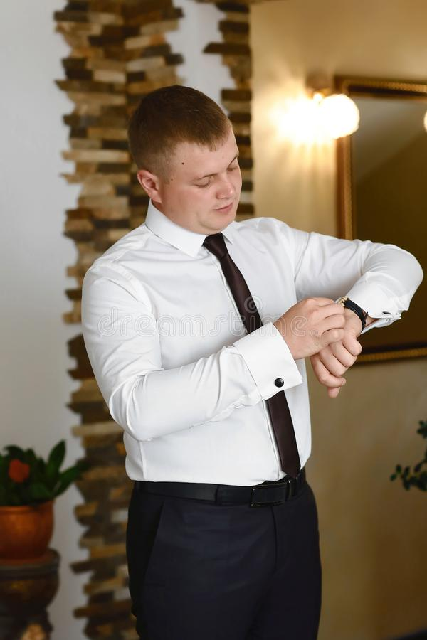 Mężczyzna układa jego buttonholes na tle biała koszula, fornal jest ubranym zegar na dzień ślubu rękawów zegarki i koszula obrazy royalty free