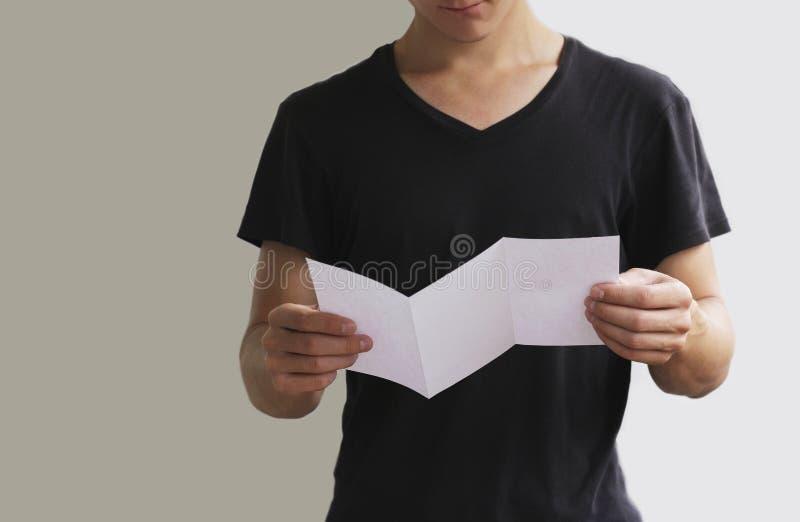 Mężczyzna ulotki broszurki czytelnicza pusta biała broszura Ulotki prezentacja Broszurowe chwyt ręki Mężczyzna przedstawienia jas fotografia stock