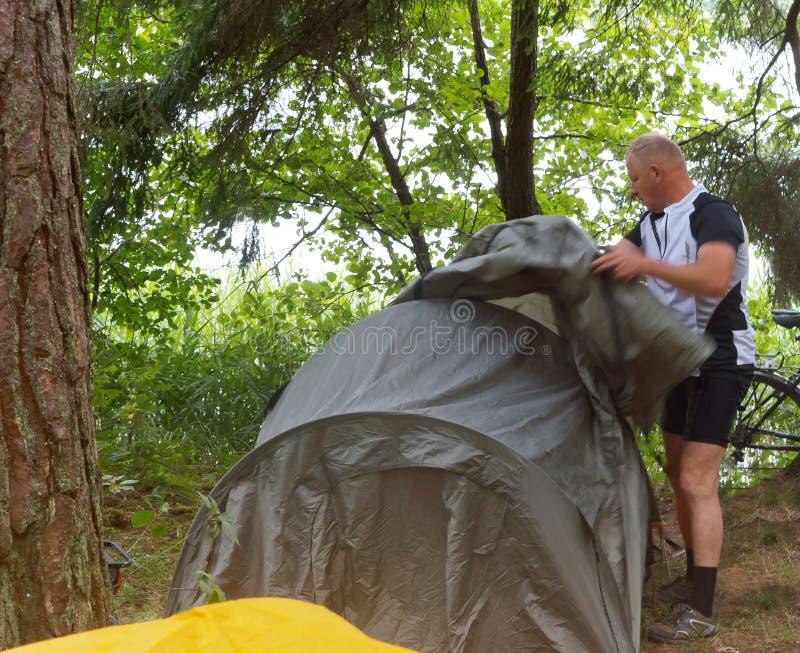 Mężczyzna ustawia turystycznego namiot, mężczyzna demontuje turystycznego namiot w lesie fotografia royalty free