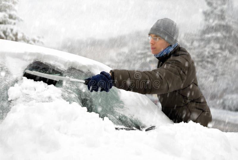 Mężczyzna usuwa śnieg od jego samochodu obraz stock
