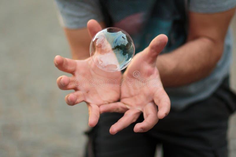 Mężczyzna utrzymuje mydlanego bąbel w jego otwartych rękach obraz royalty free
