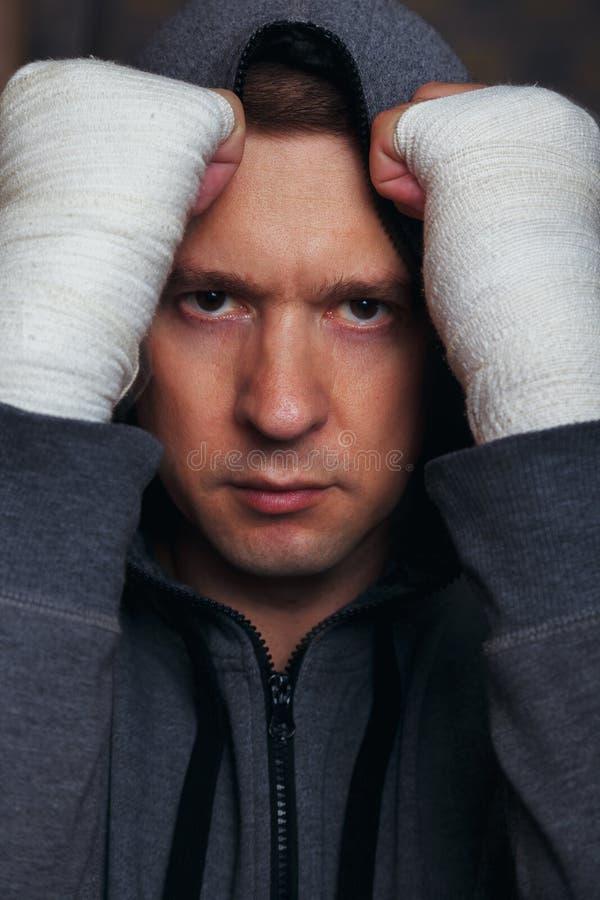 Mężczyzna utrzymuje pięści w boksu bandażu przed osobą w sport kurtce z kapiszonem obraz royalty free