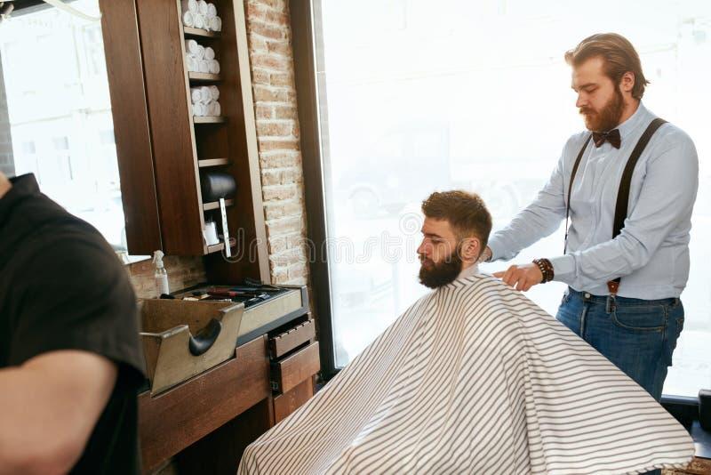 Mężczyzna Włosiany salon Mężczyzna Dostaje ostrzyżenie W fryzjera męskiego sklepie zdjęcie royalty free