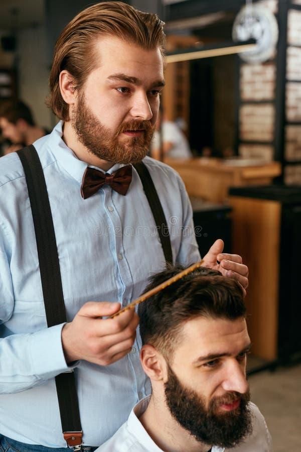 Mężczyzna Włosiany salon Mężczyzna fryzjer męski Robi fryzurze W zakładzie fryzjerskim fotografia royalty free