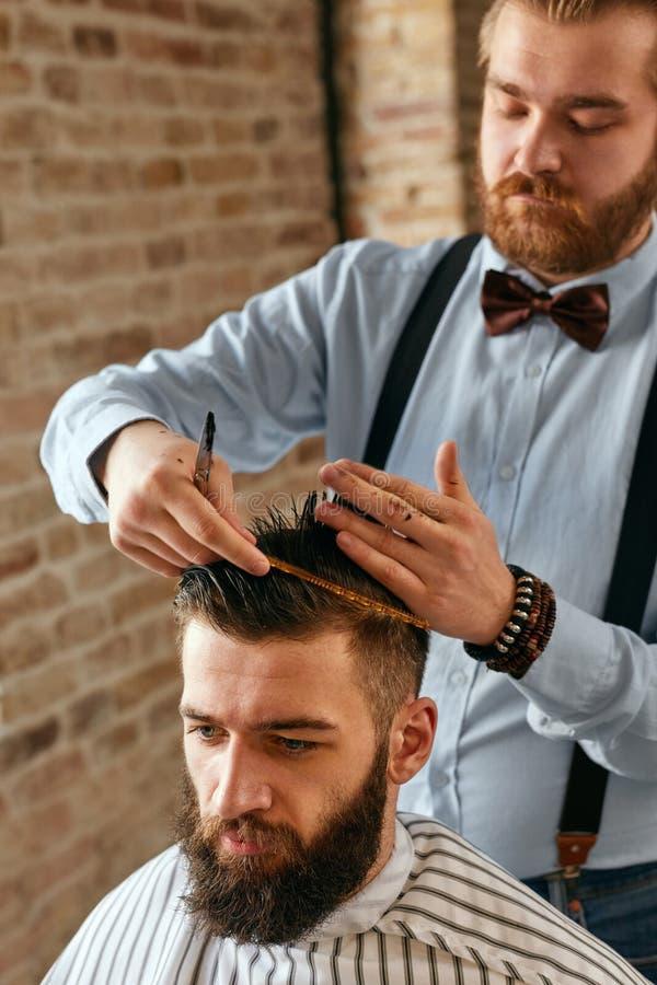 Mężczyzna Włosiany salon Fryzjer męski Robi ostrzyżeniu W zakładzie fryzjerskim obraz royalty free
