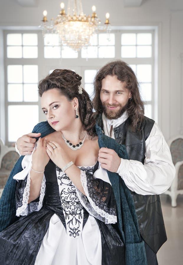 Mężczyzna w średniowiecznej kostium pokrywy pięknej kobiecie jego żakietem fotografia stock
