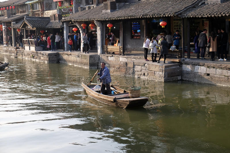 Mężczyzna w antycznej drewnianej łodzi na wodnych kanałach Xitang miasteczko w Chiny zdjęcia royalty free
