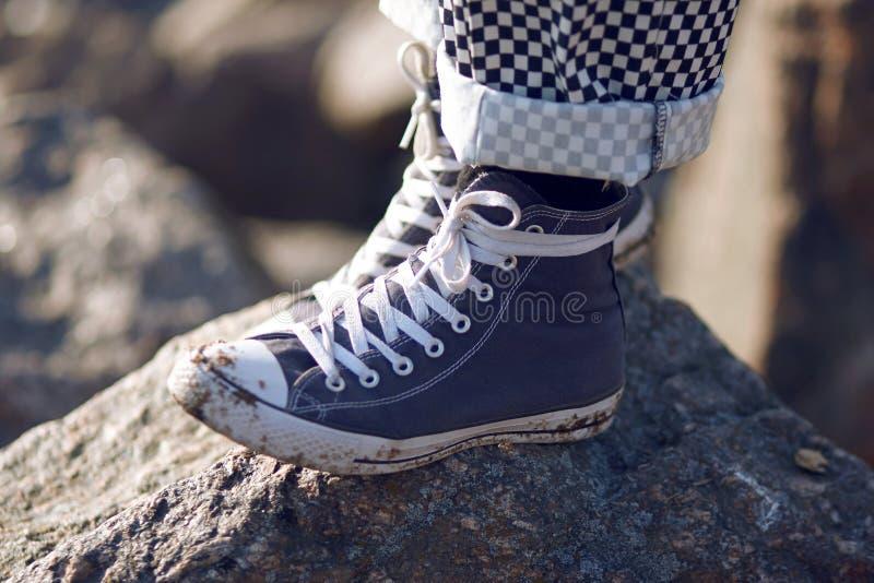 Mężczyzna w błękitów sneakers brudnych stojakach na skale fotografia royalty free