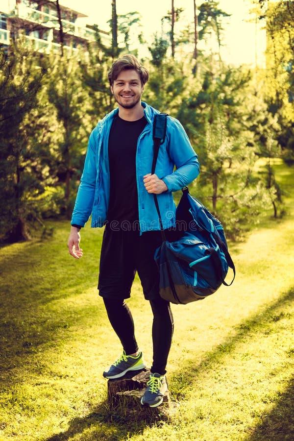 Mężczyzna w błękitów sportów kurtce z sportami zdojest zdjęcie stock