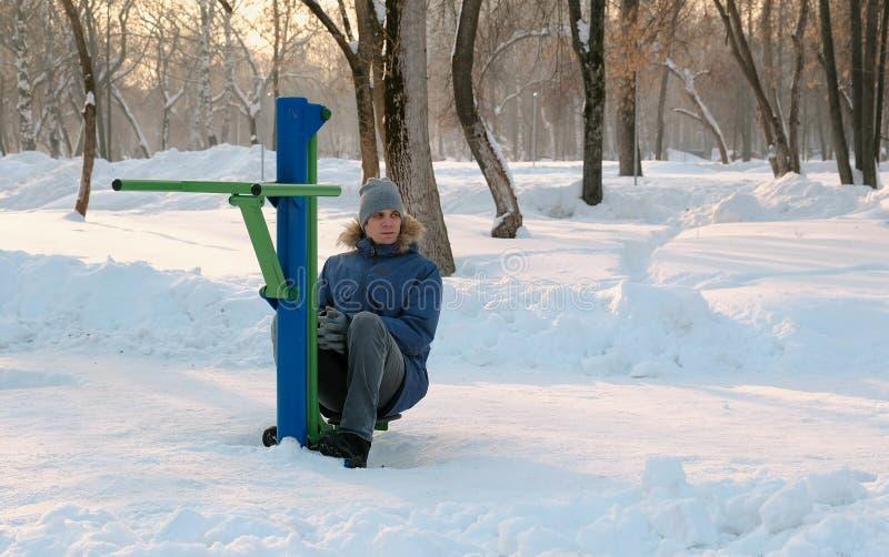 Mężczyzna w błękita puszka kurtce z kapiszonem robi nóg ćwiczeniom na symulancie w zima parku Frontowy widok obraz stock