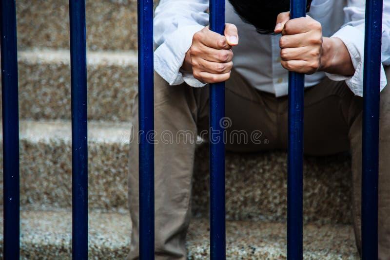 Mężczyzna w błękitnego kołnierza koszula i czarni zastoje za odprasowywamy ogrodzenie, ręki mienia żelaza ogrodzenie z sensem bez obrazy royalty free
