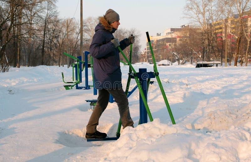 Mężczyzna w błękitnej puszek kurtce z kapiszonem angażuje w narciarskim symulancie w zimy miasta parku Boczny widok zdjęcia stock
