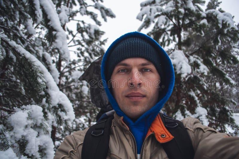 Mężczyzna w błękitnym kapiszonie bierze selfie w zima lesie na tle śnieżyści drzewa, spacer w zimie obraz royalty free