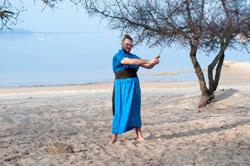 Mężczyzna w błękitnym kimonie z paskiem, babeczką, kijami, i obraz stock