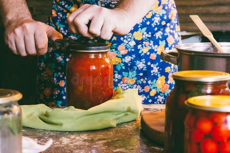 mężczyzna w barwionym fartuchu zatyka pomidory i Lecho kumberland w szkle zgrzyta w domu wiejskim obrazy stock