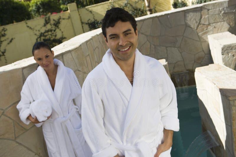 Mężczyzna W Bathrobe Z kobiety mienia ręcznikiem W tle zdjęcie stock