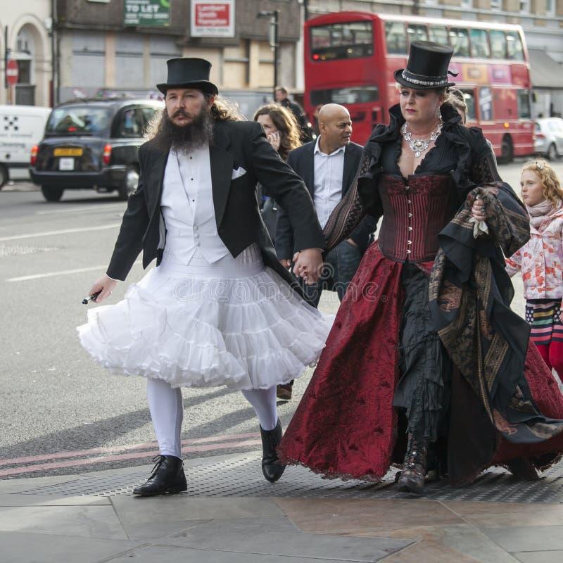Mężczyzna w białej ślubnej sukni i odgórnym kapeluszu z kobietą w gothic czerwonym aksamit sukni odprowadzenia puszku ulica w Lon obrazy stock