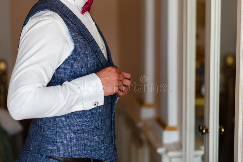 Mężczyzna w białej koszula i szarej kamizelce przymocowywa guziki przed lustrem Fornal w popielatym kostiumu i krawacie dostaje p fotografia stock