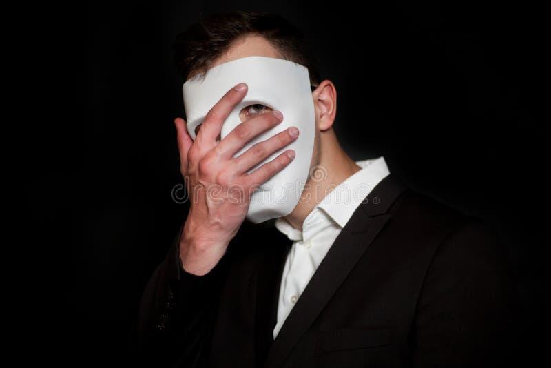 Mężczyzna w białej masce na czarnym tle Facepalm fotografia royalty free