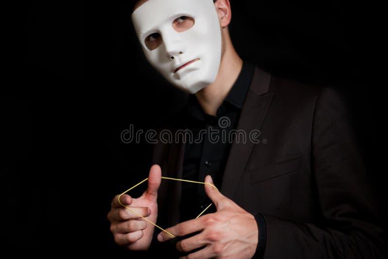 Mężczyzna w białej masce na czarnym tle W jego rękach, gumowego zespołu obrazy royalty free