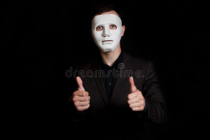 Mężczyzna w białej masce na czarnym tle Pokazuje dużego palec w dwa ręce zdjęcie royalty free