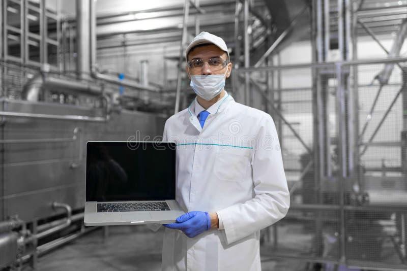 Mężczyzna w białym kontuszu i masce z laptopem w jego rękach jest przy fabryką obraz royalty free