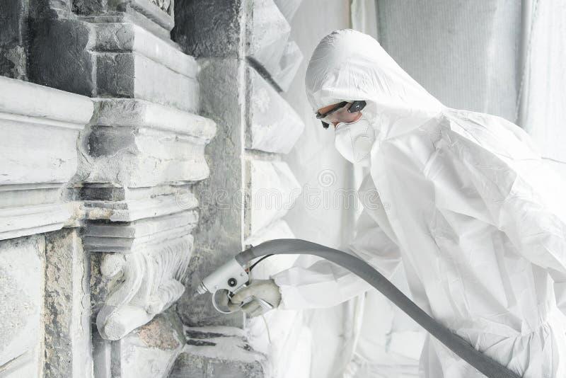 Mężczyzna w białym ochronnym mundurze czyści kamień rzeźbiącą rzeźbę od betonu i brudu z sandblasting maszyną zdjęcie stock