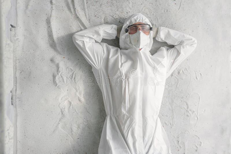 Mężczyzna w białym ochronnym mundurze, respiratorze i plastikowych przejrzystych szkłach, zdjęcia royalty free