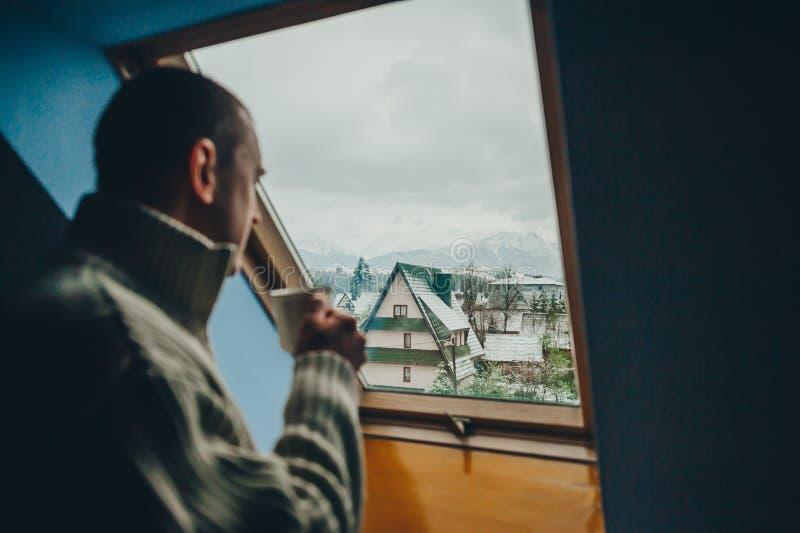 Mężczyzna w białym pulowerze z filiżanka kawy jest trwanie naprzeciw okno i jest przyglądającym pięknym miasteczkiem obraz stock