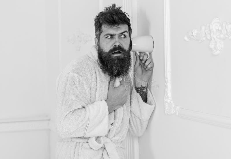 Mężczyzna w białym wewnętrznym przeszpiegi, podsłuch Sekret i szpiega pojęcie Mężczyzna z brodą i wąsy podsłuchuje używać kubek zdjęcie stock