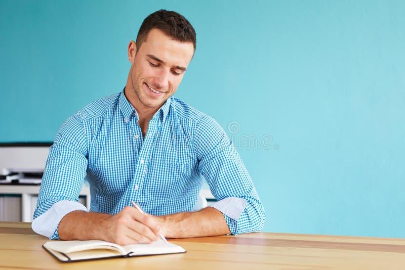 Mężczyzna w biurowym writing planie w dzienniczku zdjęcia stock