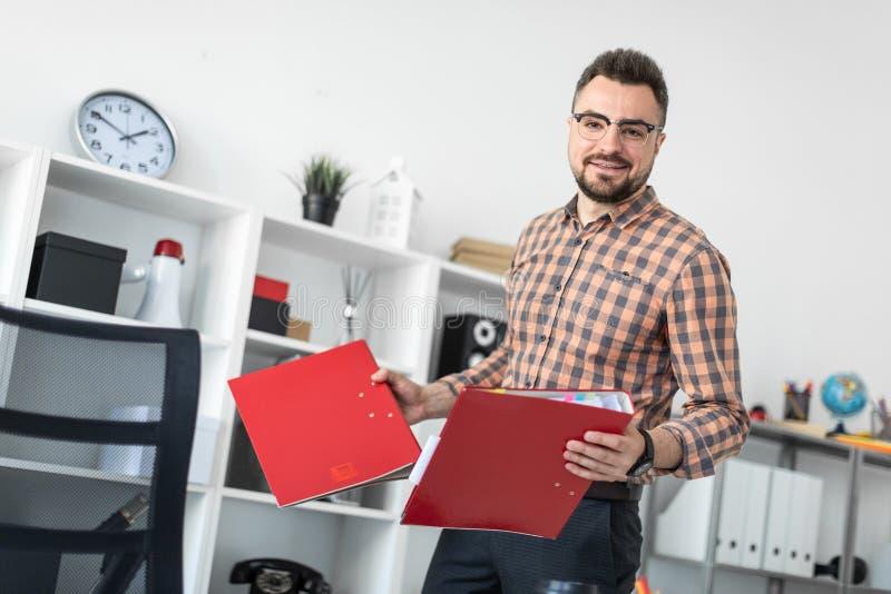 Mężczyzna w biurze ciągnie out falcówki od stojaka zdjęcia stock