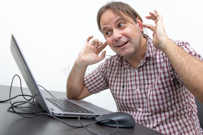 mężczyzna w biurze słucha dźwięka od małej słuchawki zdjęcia stock