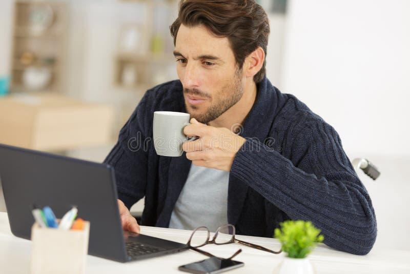 Mężczyzna w biurze z kawą na laptopa obrazy royalty free