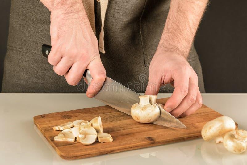Mężczyzna w ciemnym fartuchu ciie szampinionu w plasterki Przygotowanie pieczarki dla gotować fotografia stock