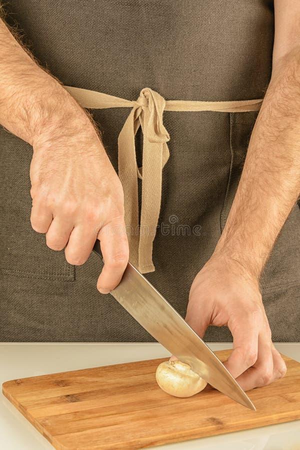 Mężczyzna w ciemnym fartuchu ciie szampiniony na drewnianej desce siekać pieczarki zdjęcie stock