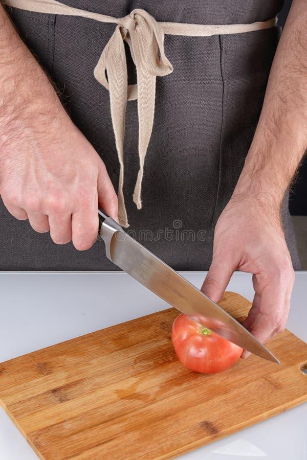 Mężczyzna w ciemnym fartuchu pokrajać pomidoru w dwa połówki Kulinarni warzywa obraz stock
