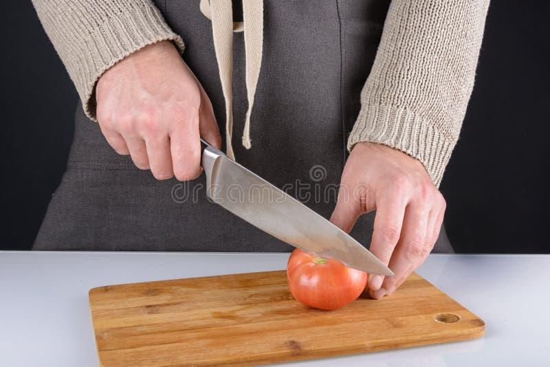 Mężczyzna w ciemnym fartuchu pokrajać pomidoru w dwa połówki Piękna fotografia proces gotować warzywa obrazy stock