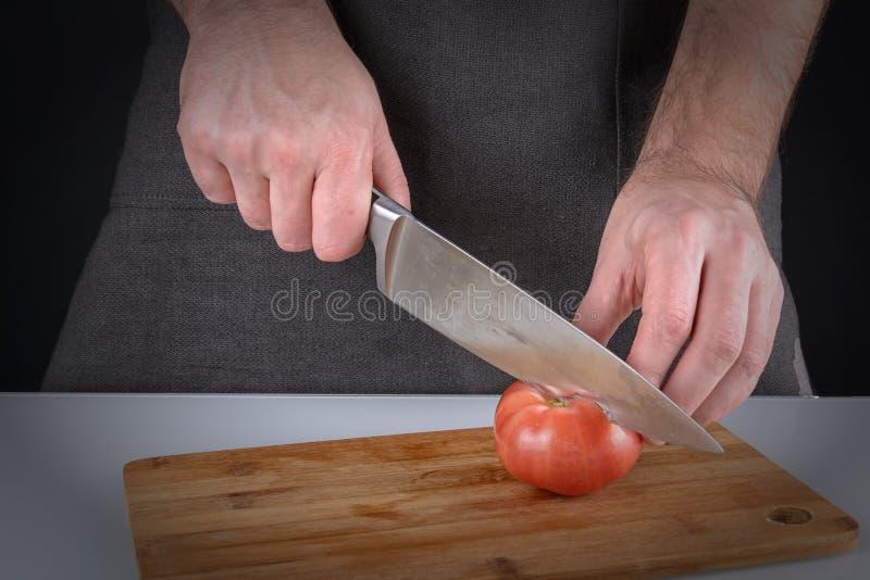Mężczyzna w ciemnym fartuchu pokrajać pomidoru w dwa połówki Piękna fotografia proces gotować warzywa z a, fotografia stock